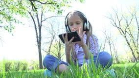 Niño que juega la tableta en el parque, muchacha con los auriculares en la hierba al aire libre en el verano 4K almacen de video