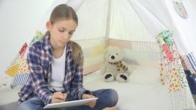 Niño que juega la tableta en la muchacha de la sala de juegos que escribe la preparación para el patio del niño de la escuela imágenes de archivo libres de regalías