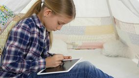 Niño que juega la tableta en la muchacha de la sala de juegos que escribe la preparación para el patio del niño de la escuela almacen de video