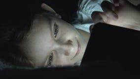 Niño que juega la tableta en la noche oscura, Internet de la ojeada de la muchacha en la cama, no durmiendo imagen de archivo