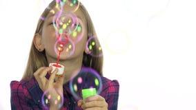Niño que juega las burbujas de jabón, globos que soplan sonrientes felices de la muchacha, pantalla blanca metrajes