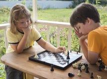 Niño que juega los outdors del ajedrez, muchacho joven que hace un movimiento Fotografía de archivo libre de regalías