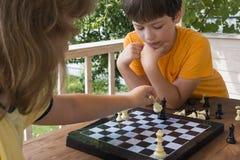 Niño que juega los outdors del ajedrez, muchacho joven que hace un movimiento Fotos de archivo libres de regalías