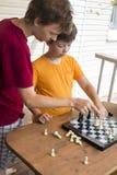 Niño que juega los outdors del ajedrez, muchacho joven que hace un movimiento Imágenes de archivo libres de regalías