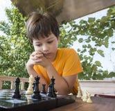 Niño que juega los outdors del ajedrez, muchacho joven que hace un movimiento Imagen de archivo libre de regalías