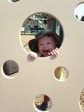 Niño que juega Peekaboo en el patio Imágenes de archivo libres de regalías