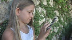 Niño que juega Smartphone por la pared de piedra en la yarda, aplicaciones tableta, niño de la muchacha al aire libre imagen de archivo
