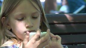 Niño que juega Smartphone, tableta en el patio en el parque, muchacha que se sienta en el banco 4K metrajes