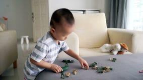 Niño que juega soldados y los juguetes de la estatuilla metrajes