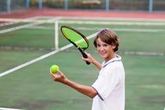 Niño que juega a tenis en corte al aire libre Imagen de archivo libre de regalías