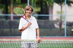 Niño que juega a tenis en corte al aire libre Fotos de archivo
