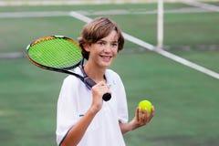 Niño que juega a tenis en corte al aire libre Imagen de archivo