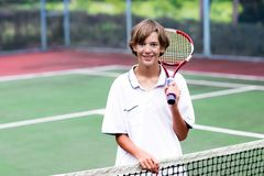 Niño que juega a tenis en corte al aire libre Fotos de archivo libres de regalías