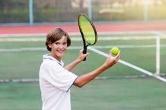 Niño que juega a tenis en corte al aire libre Imagenes de archivo