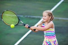 Niño que juega a tenis en corte al aire libre fotografía de archivo libre de regalías