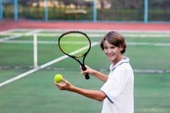 Niño que juega a tenis en corte al aire libre Fotografía de archivo