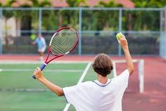 Niño que juega a tenis en corte al aire libre Foto de archivo libre de regalías