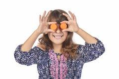 Niño que la cubre ojos con las zanahorias, promoviendo hábitos alimentarios sanos en una edad joven imagenes de archivo