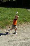 Niño que lanza una bola foto de archivo