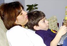 Niño que lee a la madre foto de archivo