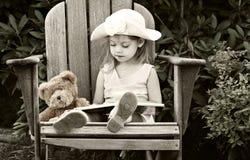 Niño que lee a su oso de peluche Imagenes de archivo