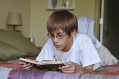 Niño que lee un libro foto de archivo