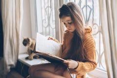 Niño que lee un libro con el gato Fotografía de archivo
