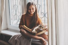 Niño que lee un libro con el gato Imagen de archivo libre de regalías