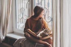 Niño que lee un libro con el gato Fotografía de archivo libre de regalías