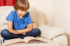 Niño que lee un libro en casa Foto de archivo libre de regalías