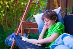 Niño que lee un libro en el jardín Foto de archivo libre de regalías