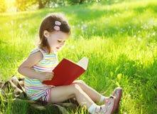 Niño que lee un libro en la hierba en verano soleado Imagenes de archivo