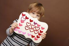 Niño que lleva a cabo el arte del día de tarjeta del día de San Valentín con los corazones Foto de archivo libre de regalías