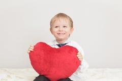 Niño que lleva a cabo el corazón Imagenes de archivo