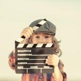 Niño que lleva a cabo el tablero de chapaleta en manos Imagenes de archivo