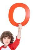 Niño que lleva a cabo la letra del alfabeto imagen de archivo libre de regalías