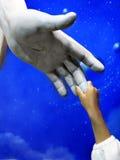 Niño que lleva a cabo la mano de Jesus Statue Imagen de archivo libre de regalías