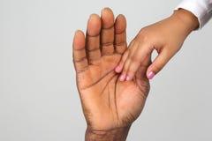 Niño que lleva a cabo la mano de un padre de piel morena Imagen de archivo libre de regalías