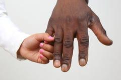 Niño que lleva a cabo la mano de un padre de piel morena Imágenes de archivo libres de regalías