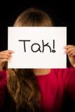 Niño que lleva a cabo la muestra con la palabra danesa Tak - gracias Imagenes de archivo