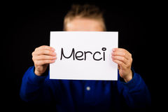 Niño que lleva a cabo la muestra con la palabra francesa Merci - gracias imágenes de archivo libres de regalías