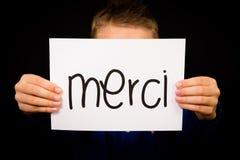 Niño que lleva a cabo la muestra con la palabra francesa Merci - gracias imagenes de archivo