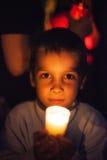 Niño que lleva a cabo la vela Imagen de archivo