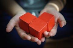 Niño que lleva a cabo los bloques de madera: forma roja del corazón fotos de archivo libres de regalías
