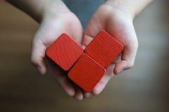 Niño que lleva a cabo los bloques de madera: forma roja del corazón Foto de archivo