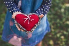 Niño que lleva a cabo un corazón rojo en las manos, primer de la Navidad Fotografía de archivo