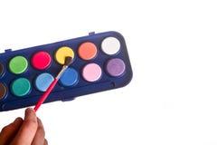 Niño que lleva a cabo un sistema de la pintura del watercolour Foto de archivo libre de regalías