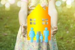 Niño que lleva a cabo una casa e iconos familiy como concepto de la vivienda, hacia fuera imágenes de archivo libres de regalías