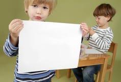 Niño que lleva a cabo una muestra de la página en blanco Imagenes de archivo
