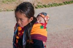 Niño que lleva de la muchacha de Hmong en su mochila. Sapa. Vietnam Foto de archivo libre de regalías